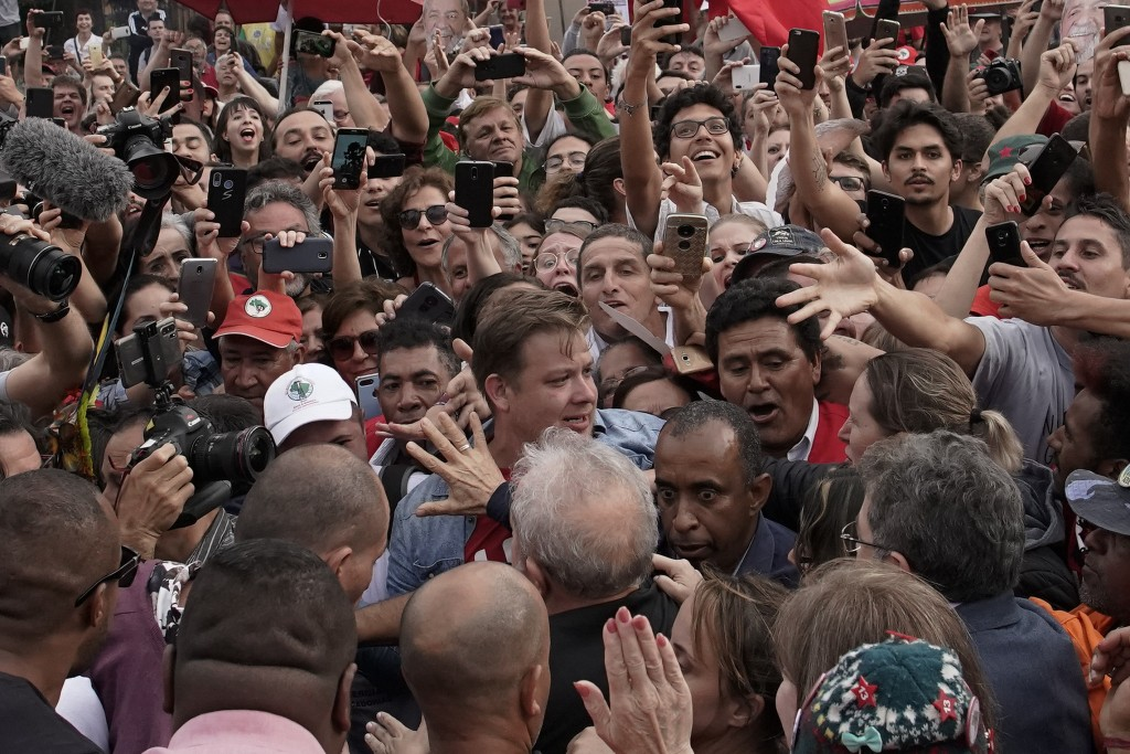 Brazil's former President Luiz Inacio Lula da Silva, bottom, back to camera, waves to supporters as he exits the the Federal Police headquarters where...