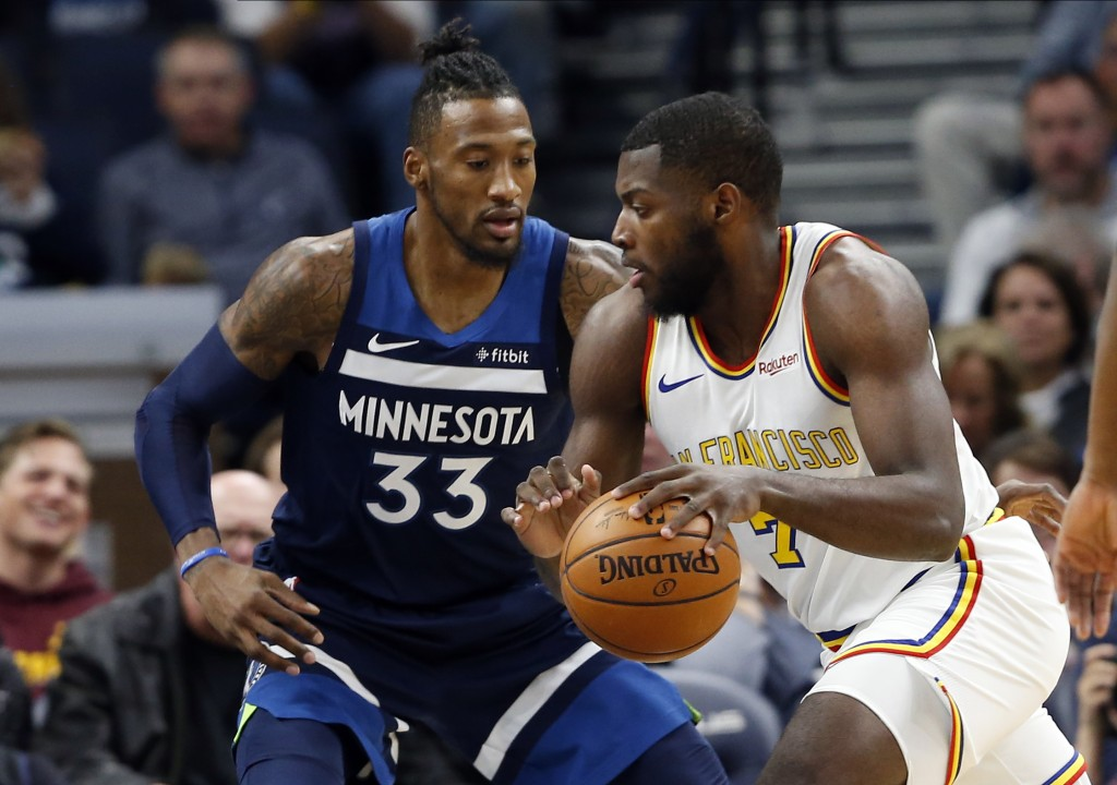 Golden State Warriors' Eric Paschall, right, drives around against the Minnesota Timberwolves' Minnesota Timberwolves' Robert Covington in the first h...