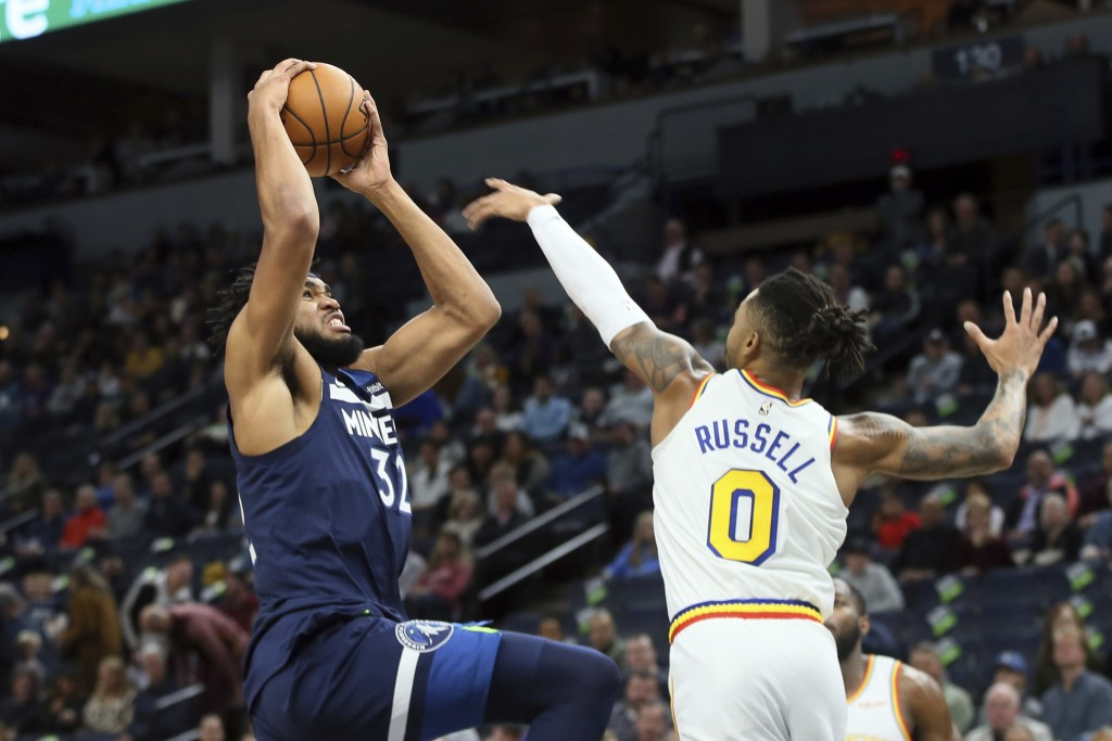 Minnesota Timberwolves' Karl-Anthony Towns, left, as Golden State Warriors' D'Angelo Russell defends in the first half of an NBA basketball game Frida...
