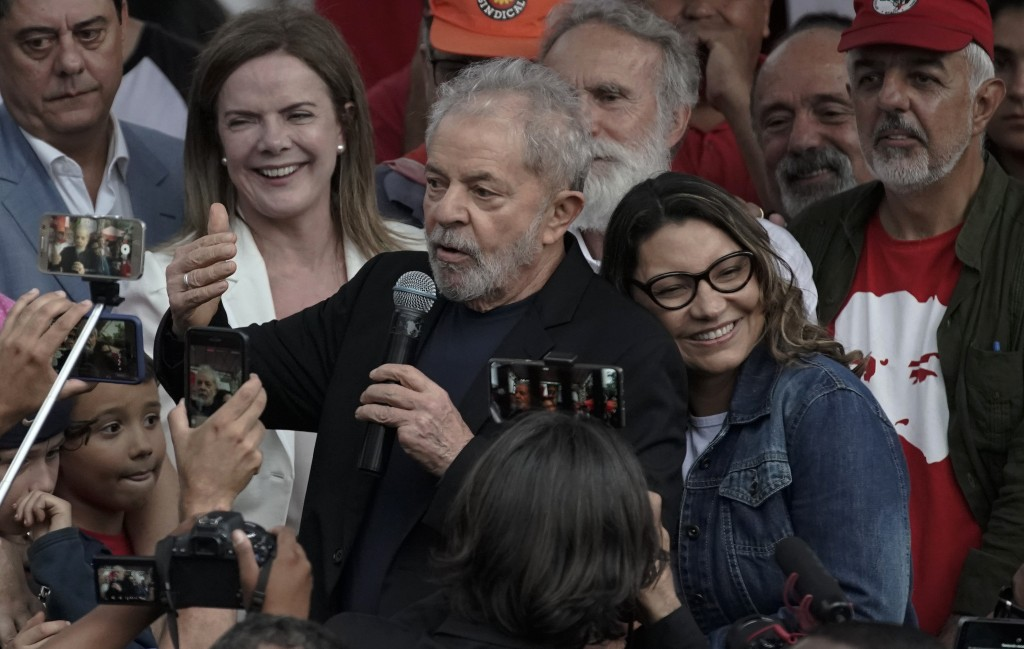 Brazil's former President Luiz Inacio Lula da Silva speaks to supporters as his girlfriend Rosangela da Silva leans on his back after he was released ...