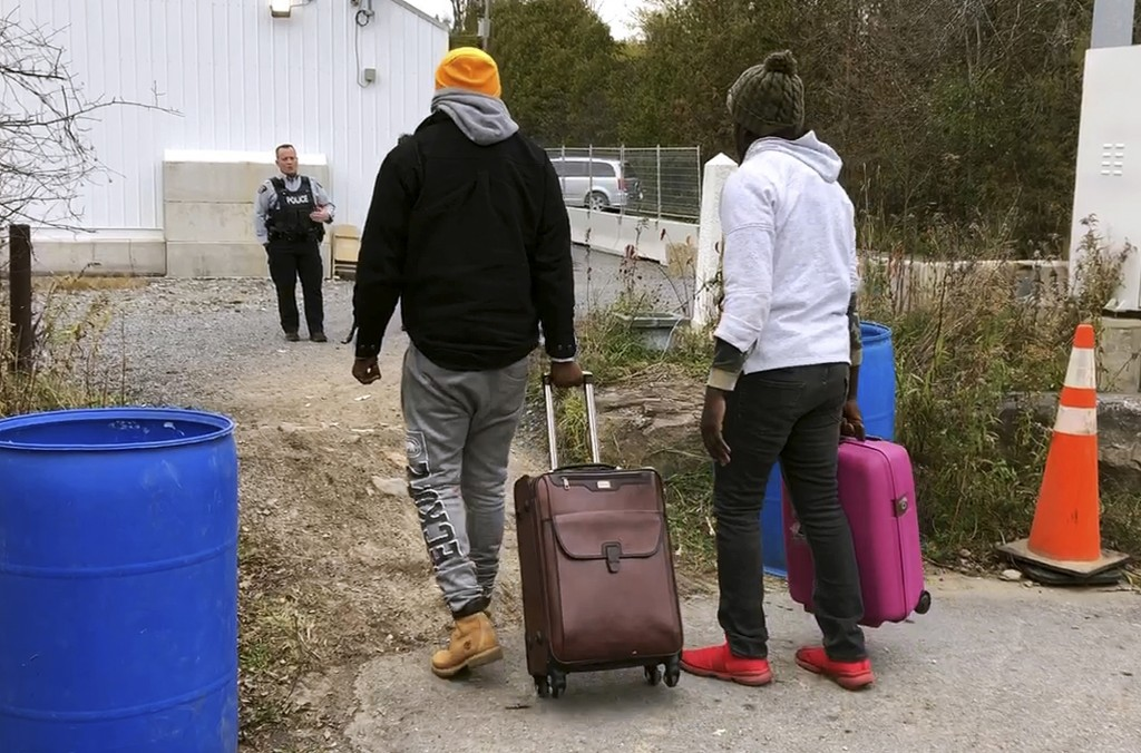In this Nov. 4, 2019, photo, two men from Nigeria illegally cross the U.S. border at Roxham Road in Champlain, N.Y., into Canada where Royal Canadian ...