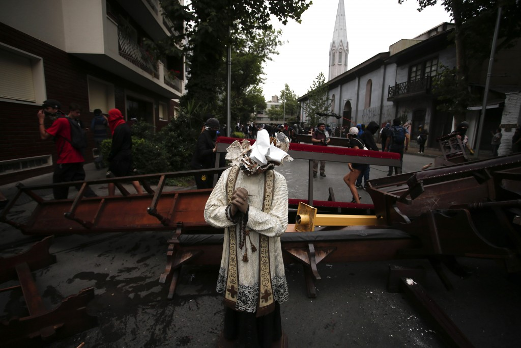 A damaged statue taken from a church forms part of barricade created by anti-government protesters, in Santiago, Chile, Friday, Nov. 8, 2019. Chile's ...