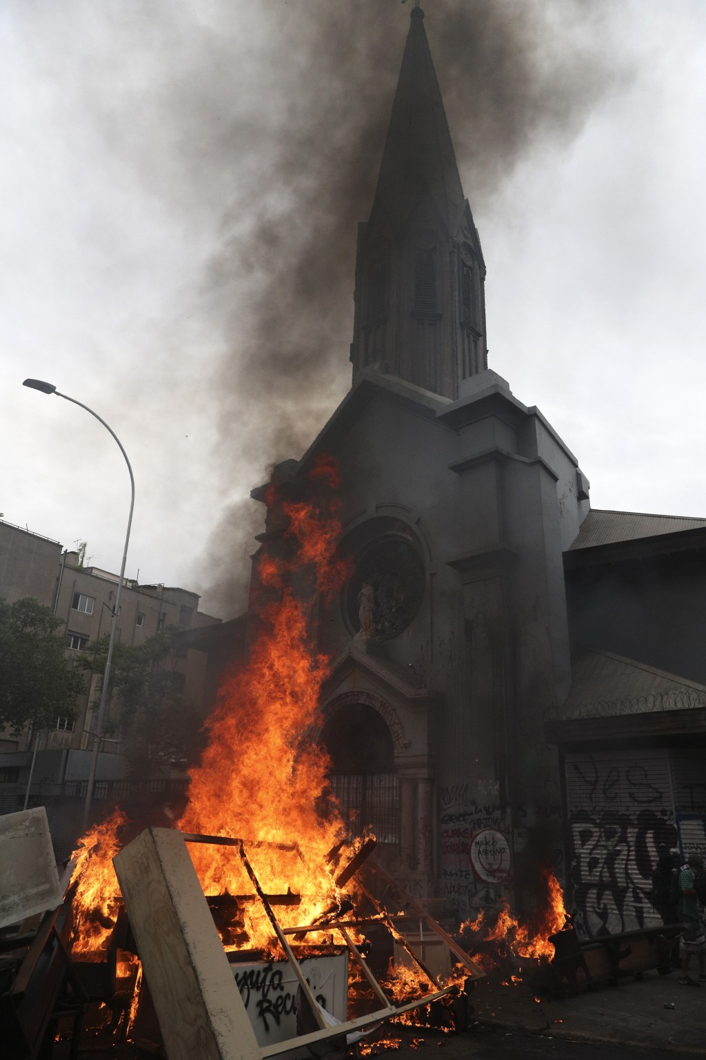 Items removed from a church by anti-government protesters go up in flames in a barricade they built, in Santiago, Chile, Friday, Nov. 8, 2019. Chile's...