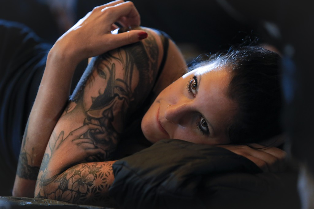 In this Saturday, Nov. 2, 2019, a woman lies on a bed while getting a tattoo on her leg during the 10th International Tattoo Convention in Bucharest, ...