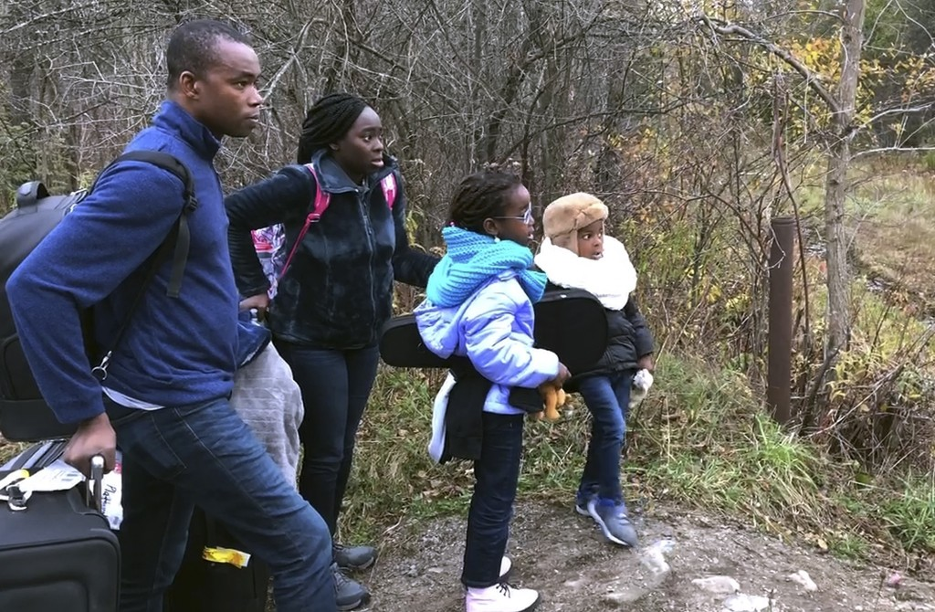 In this Nov. 4, 2019, photo, a family from Nigeria waits to illegally cross the U.S. border at Roxham Road in Champlain, N.Y., into Canada where Royal...