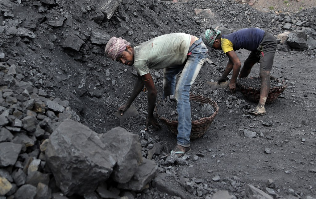 In this Oct. 23, 2019, photo, laborers fill baskets with coal before loading it into trucks for transportation in the village of Godhar in Jharia,, a ...