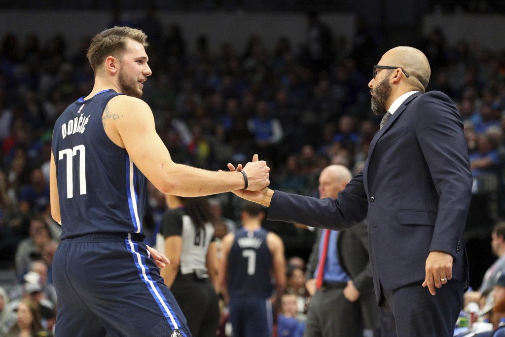 Dallas Mavericks guard Luka Doncic (77) shakes hands with New York Knicks head coach David Fizdale in the first half of an NBA basketball game Friday,...