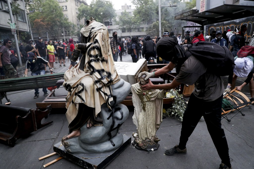 An anti-government protester beheads a statue of Jesus Christ that was taken from a church to be added to a barricade, in Santiago, Chile, Friday, Nov...
