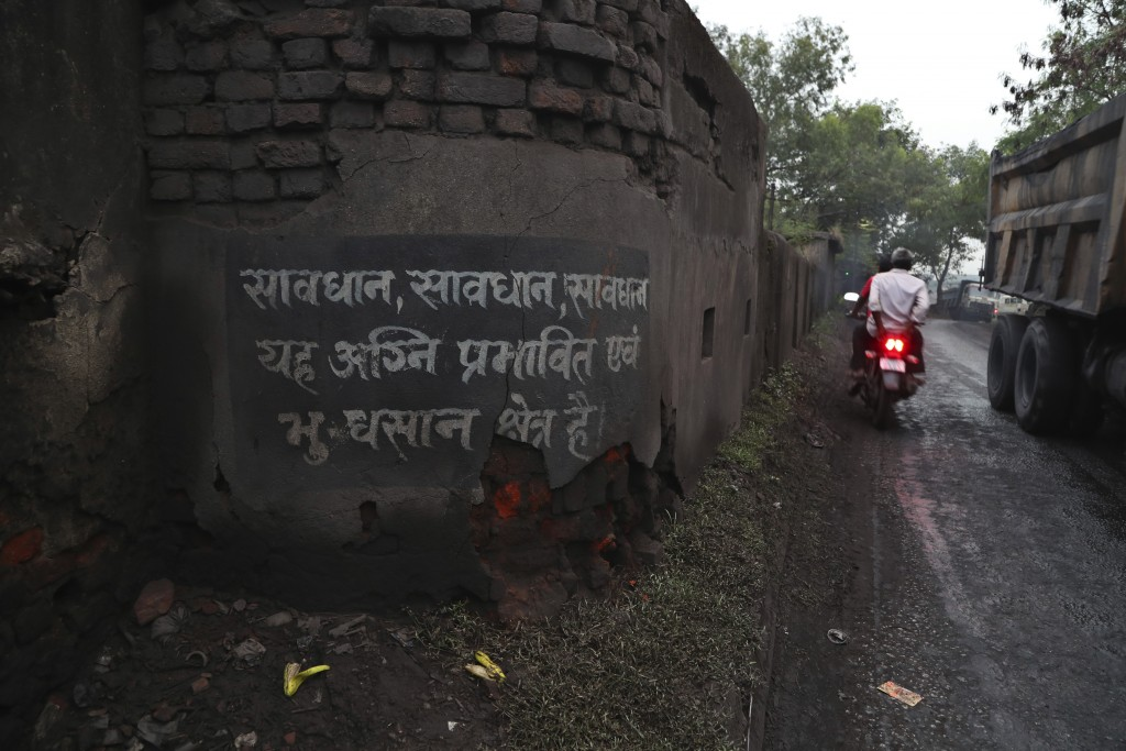 In this Oct. 23, 2019, photo, a motorist rides past a warning painted on a wall informing people about the burning coal mine zone and land subsidence ...