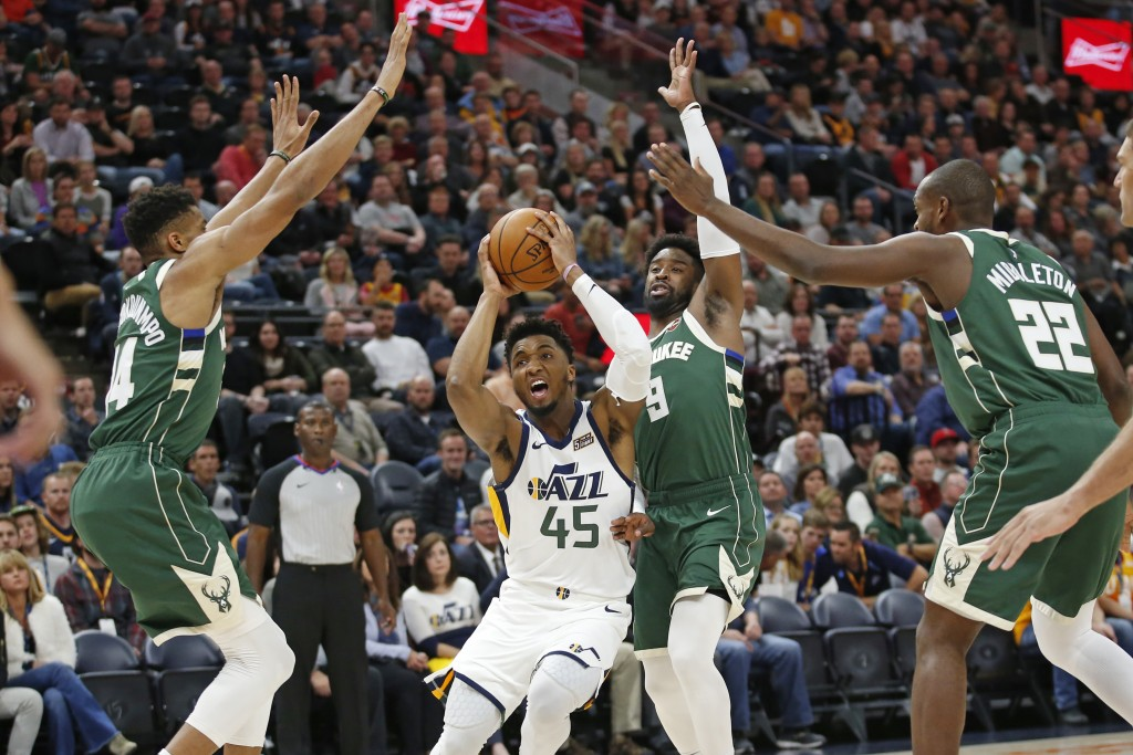 Utah Jazz guard Donovan Mitchell (45) drives to the basket as Milwaukee Bucks' Wesley Matthews (9), Giannis Antetokounmpo (34) and Khris Middleton (22...