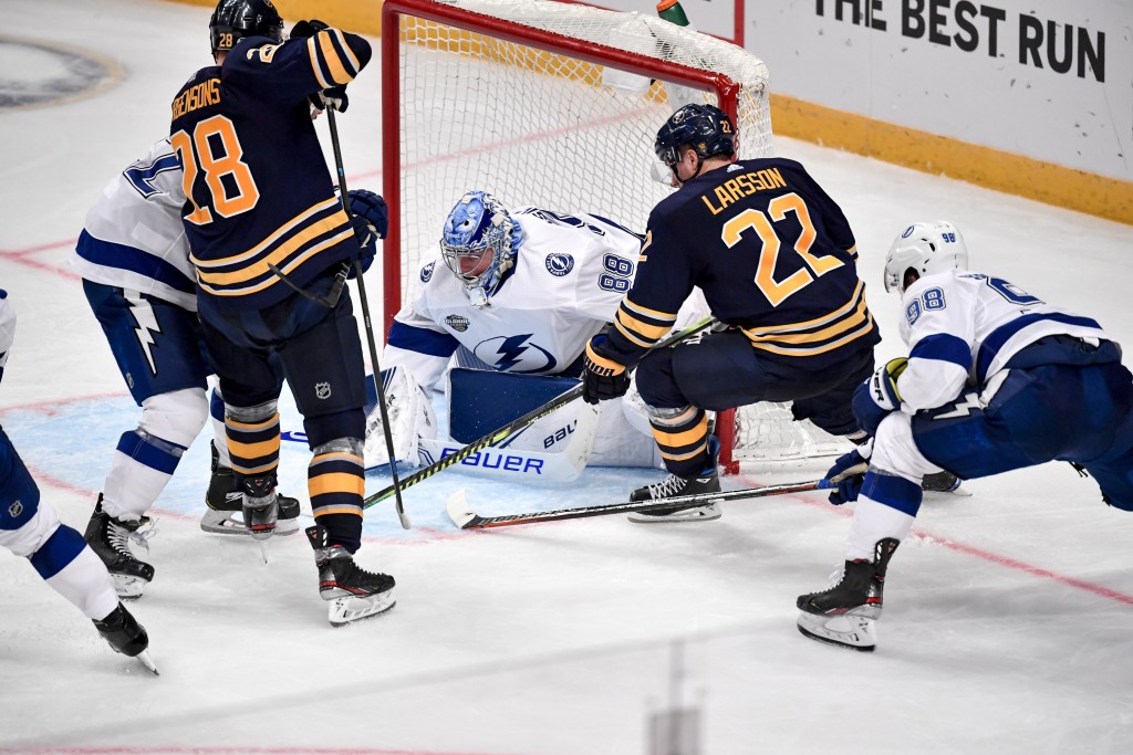Buffalo Sabres' Zemgus Girgensons (28) and Johan Larsson (22) go after the puck in front of Tampa Bay Lightning goalie Andrei Vasilevskiy during an NH...