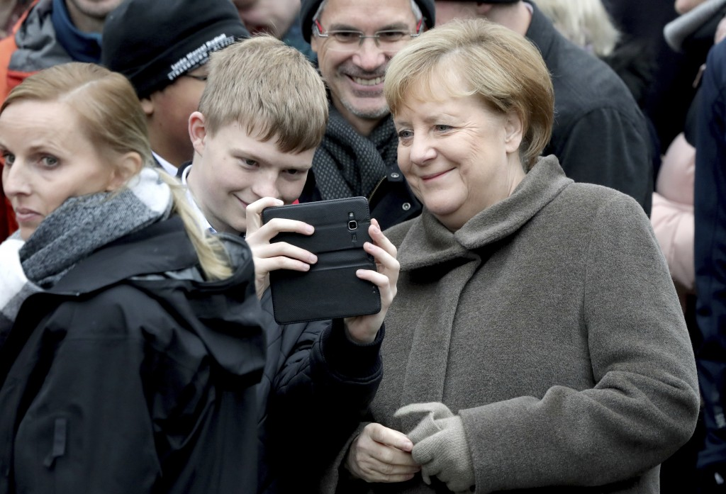 German Chancellor Angela Merkel, right, takes a selfie with a visitor prior to a memorial service for the 30th anniversary of the fall of the Wall in ...