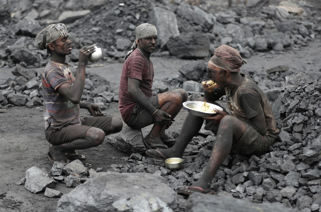 In this Oct. 23, 2019, photo, laborers eat lunch at a coal loading site in the village of Godhar in Jharia, a remote corner of eastern Jharkhand state...