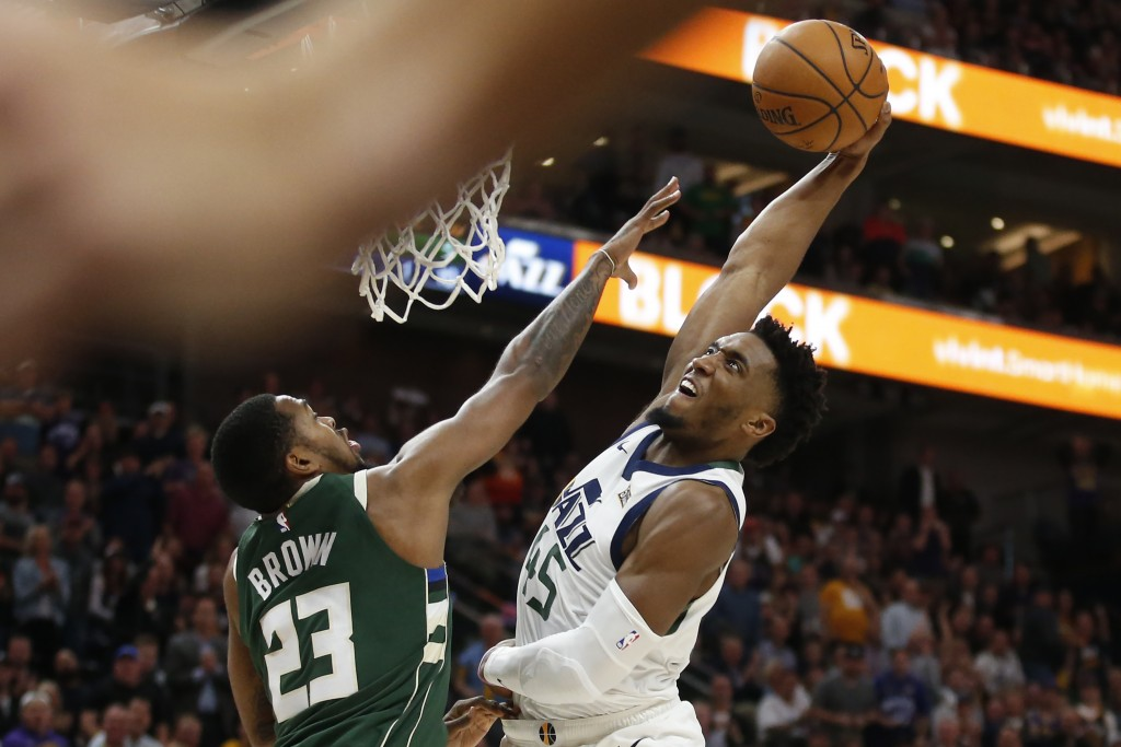Utah Jazz guard Donovan Mitchell (45) dunks on Milwaukee Bucks guard Sterling Brown (23) during the first half of an NBA basketball game Friday, Nov. ...