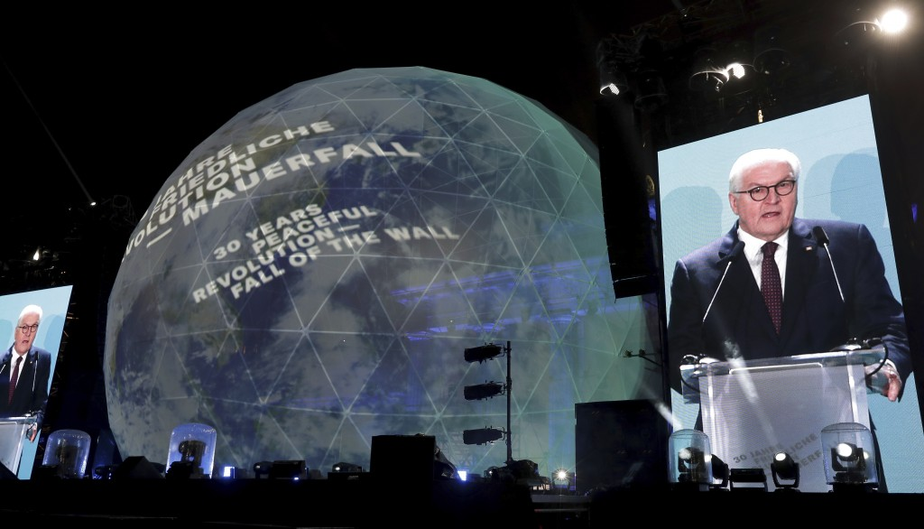 German President Frank-Walter Steinmeier is seen on giant video screens as he delivers a speech in front of the Brandenburg Gate as part of stage pres...