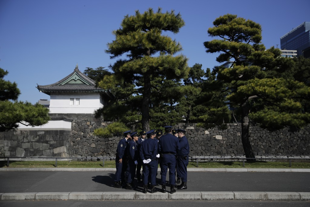 A group of police officers gather outside the Imperial Palace before the royal parade of Japanese Emperor Naruhito and Empress Masako in Tokyo, Sunday...