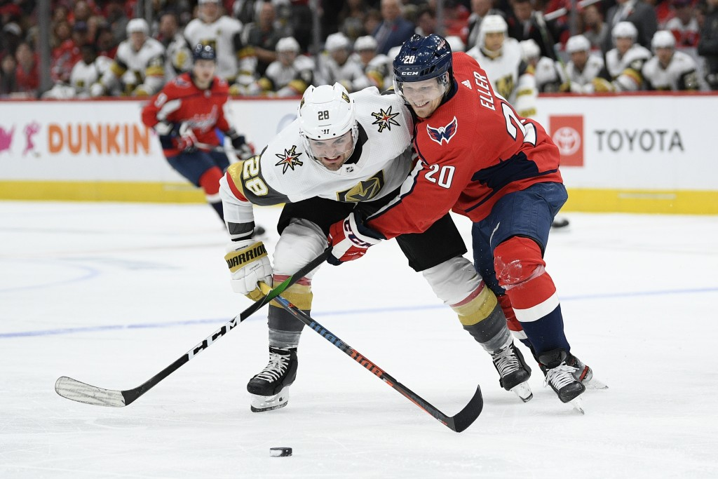 Washington Capitals center Lars Eller (20), of Denmark, and Vegas Golden Knights left wing William Carrier (28) fight fro the puck during the second p...