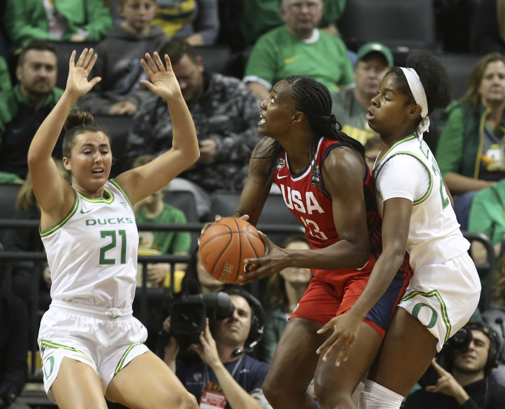 United States' Sylvia Fowles, center, looks for a shot under pressure from Oregon's Erin Boley, left, and Ruthy Hebard during the first half an exhibi...