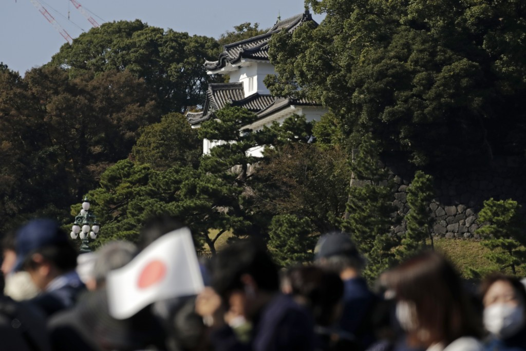 Spectators arrive at the Imperial Palace to watch the royal parade of Japanese Emperor Naruhito and Empress Masako in Tokyo, Sunday, Nov. 10, 2019. (A...