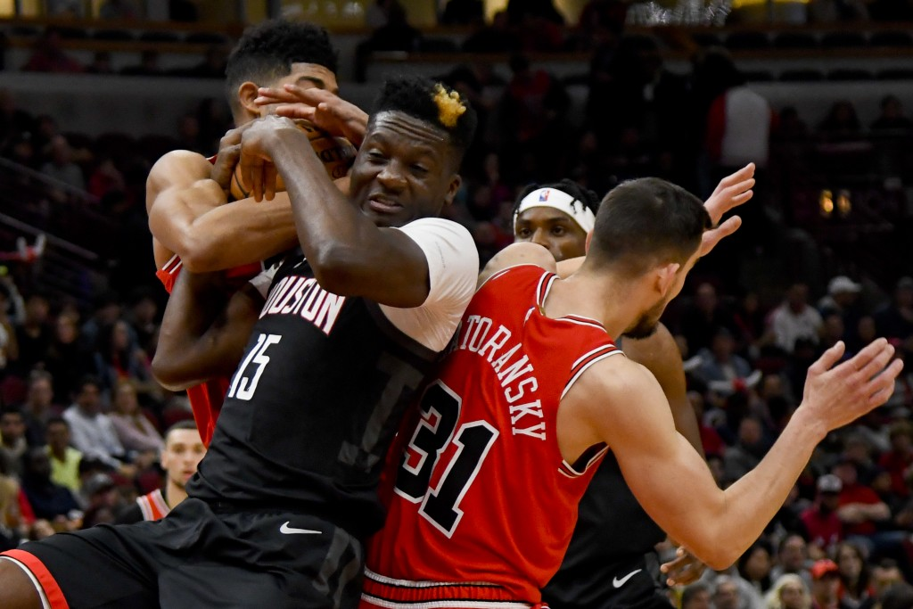 Chicago Bulls forward Chandler Hutchison, back, fights for the ball with Houston Rockets center Clint Capela (15) and guard Tomas Satoransky (31) duri...