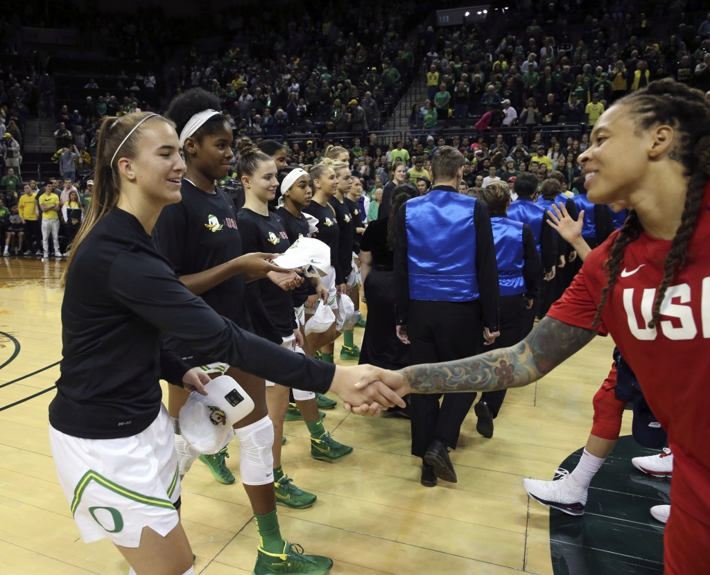 Oregon's Sabrina Ionescu, left, exchanges hats with U.S.'s Seimone Augustus before their women's exhibition basketball game in Eugene, Ore., Saturday,...