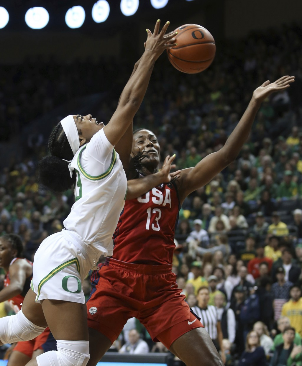 Oregon's Minyon Moore, left, is fouled while going to the basket by United States' Sylvia Fowles during the first half of an exhibition basketball gam...