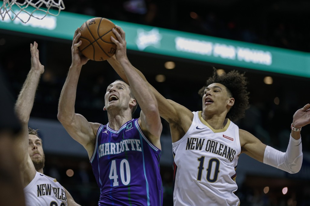 Charlotte Hornets center Cody Zeller, center, drives to the basket between New Orleans Pelicans forward Nicolo Melli, left, and New Orleans Pelicans c...