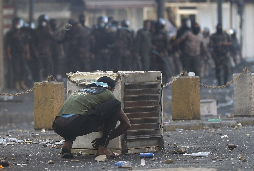 An anti-government protester crouches down during a clash with Iraqi security forces in central Baghdad, Iraq, Saturday, Nov. 9, 2019.   The protests ...