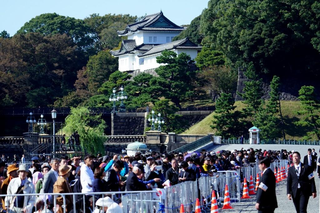 Spectators wait at the Imperial Palace before the royal parade of Japanese Emperor Naruhito and Empress Masako in Tokyo, Sunday, Nov. 10, 2019. (AP Ph...