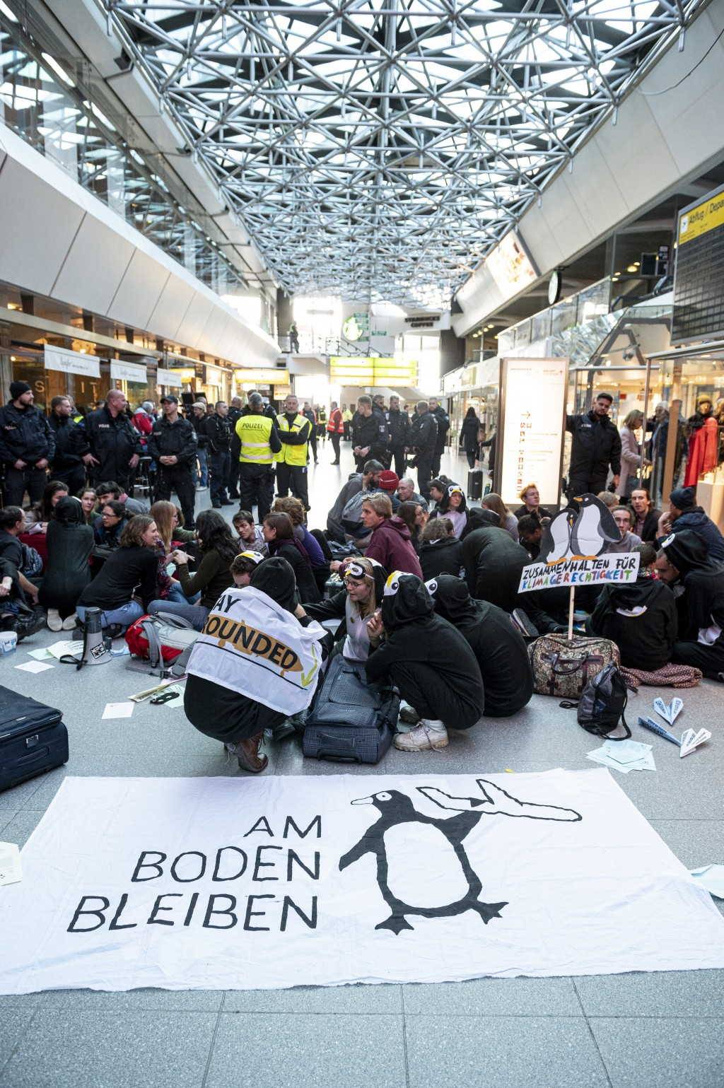 Climate activists block the entrance hall of the Tegel airport in Berlin, Germany, Sunday, Nov. 10, 2019.A banner reads 'stay on the ground'.  (Fabian...