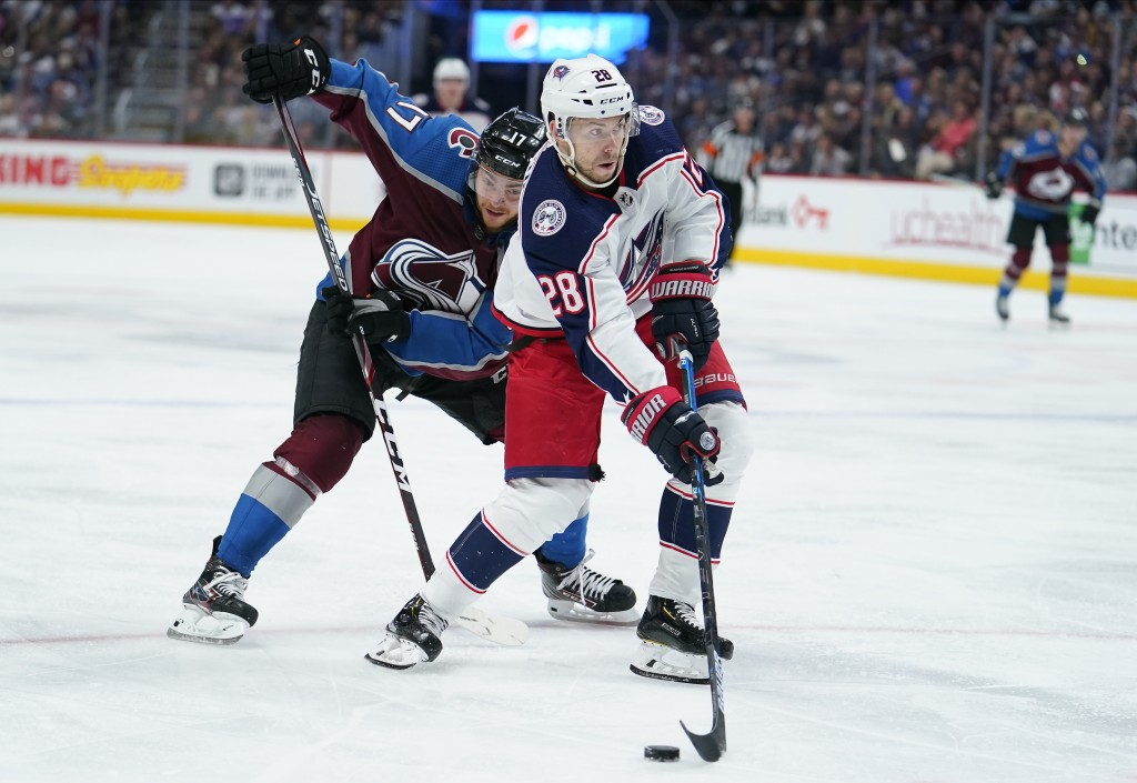Columbus Blue Jackets right wing Oliver Bjorkstrand (28) moves the puck past Colorado Avalanche center Tyson Jost (17) during the third period of an N...