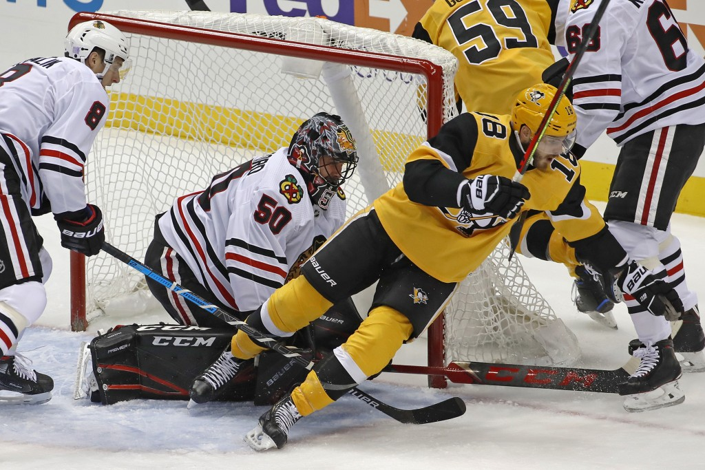Pittsburgh Penguins' Alex Galchenyuk (18) collides with Chicago Blackhawks goaltender Corey Crawford (50) during the first period of an NHL hockey gam...