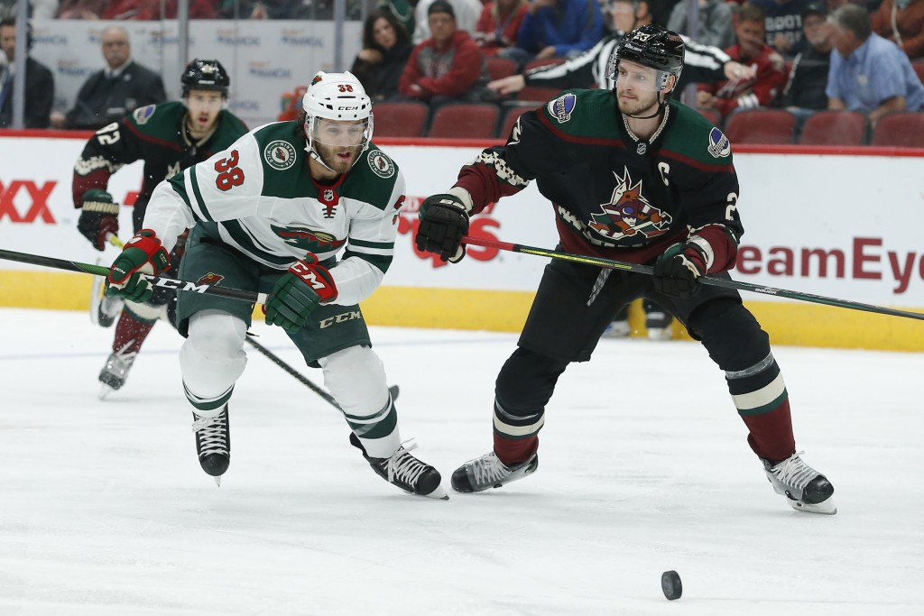 Minnesota Wild right wing Ryan Hartman (38) and Arizona Coyotes defenseman Oliver Ekman-Larsson chase the puck in the first period during an NHL hocke...