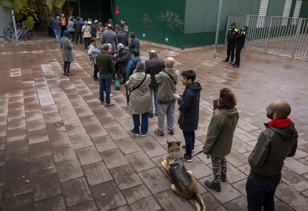People line up outside a polling station to cast their vote for the general election in Barcelona, Spain, Sunday, Nov.10, 2019. Spain holds its second...