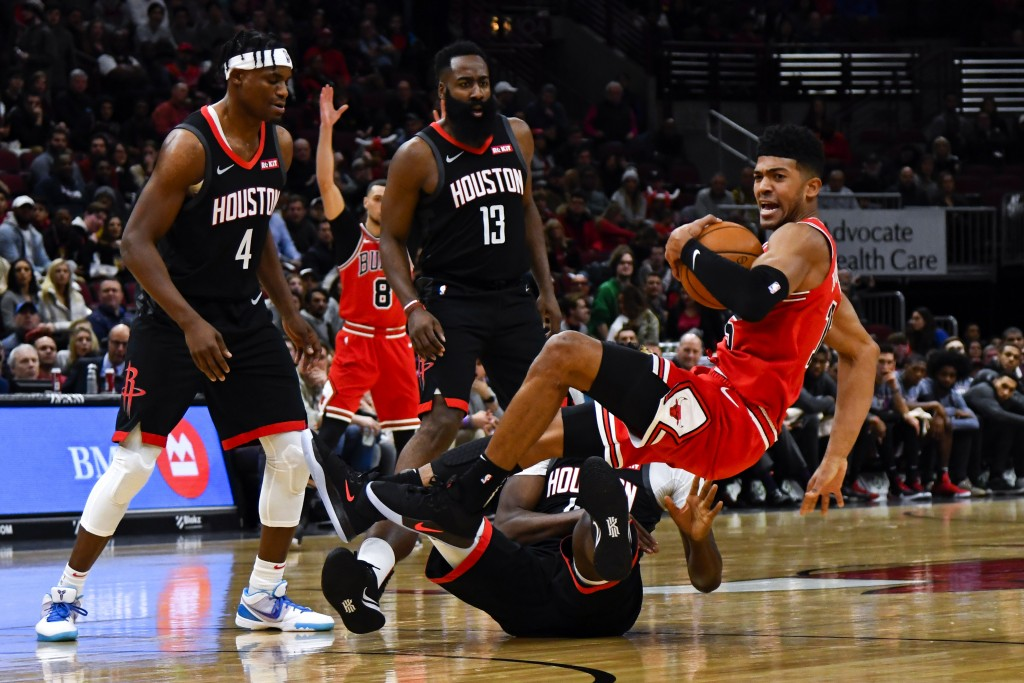 Chicago Bulls forward Chandler Hutchison, right, is flipped to the ground while fighting for the ball with Houston Rockets center Clint Capela, bottom...