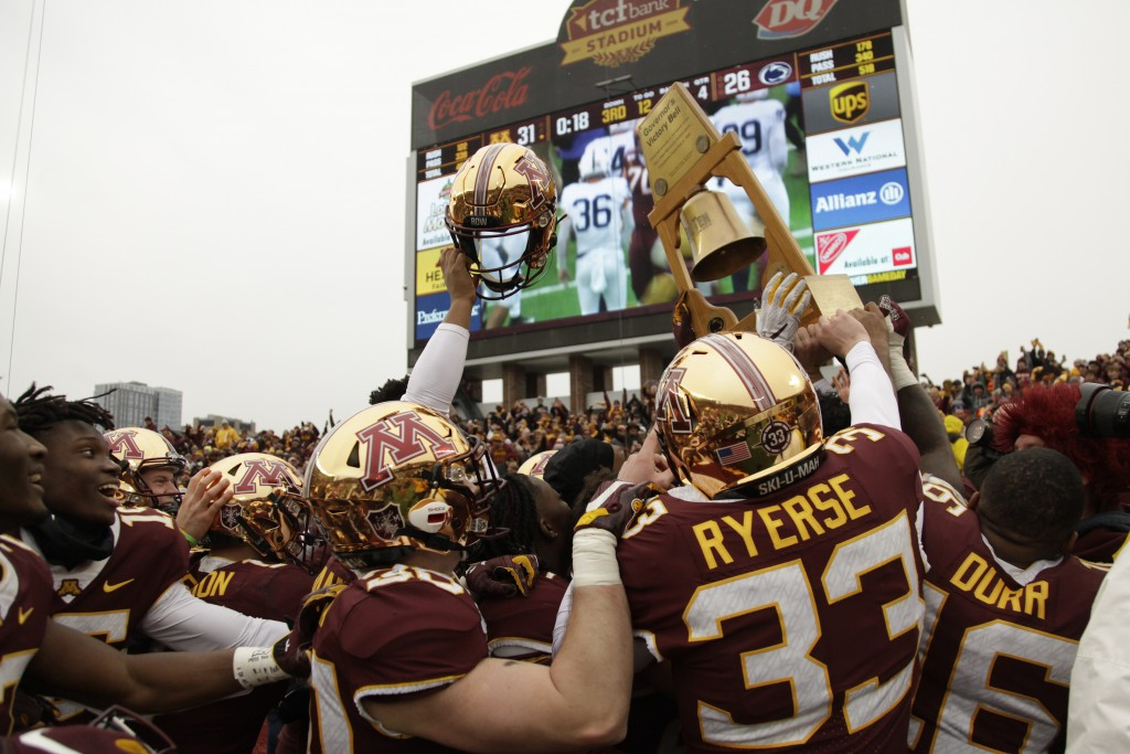 Minnesota football players hold up the Governor's Victory Bell after winning 31-26 against Penn State during an NCAA college football game Saturday, N...