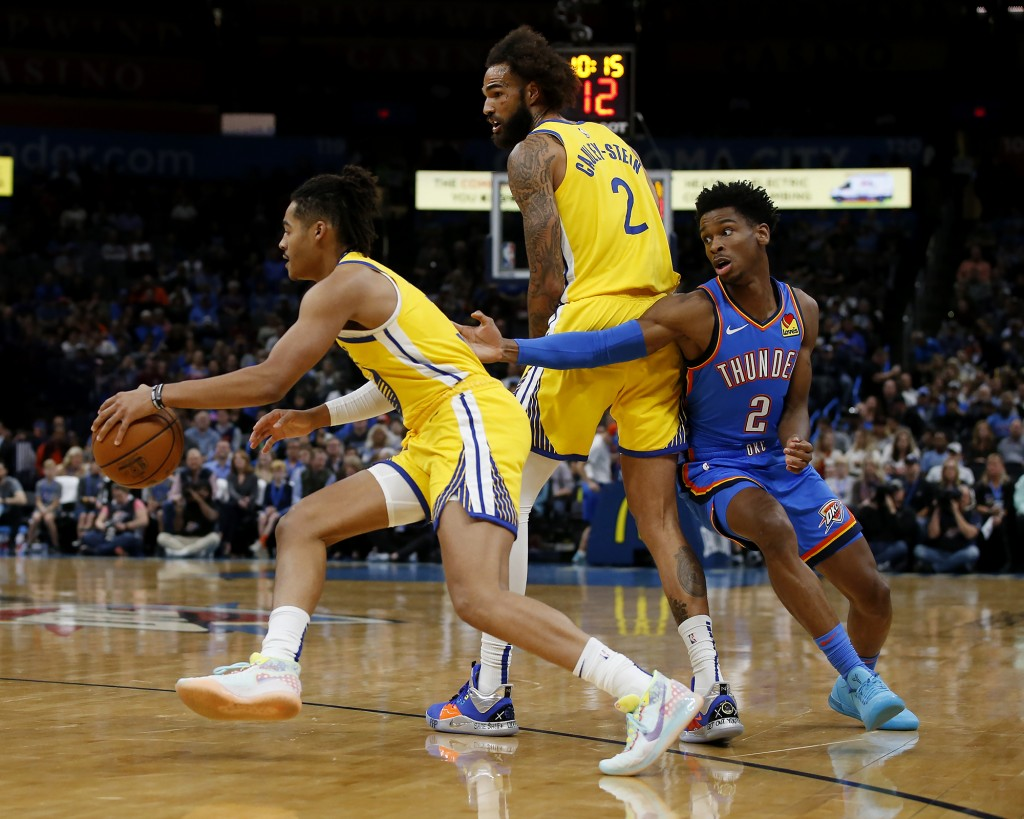 Golden State Warriors' Jordan Poole (3) drives the ball away from Oklahoma City Thunder's Shai Gilgeous-Alexander (2) while Willie Cauley-Stein (2) lo...