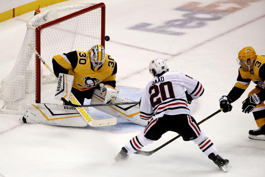 Chicago Blackhawks' Brandon Saad (20) hits the goalpost behind Pittsburgh Penguins goaltender Matt Murray (30) during the first period of an NHL hocke...