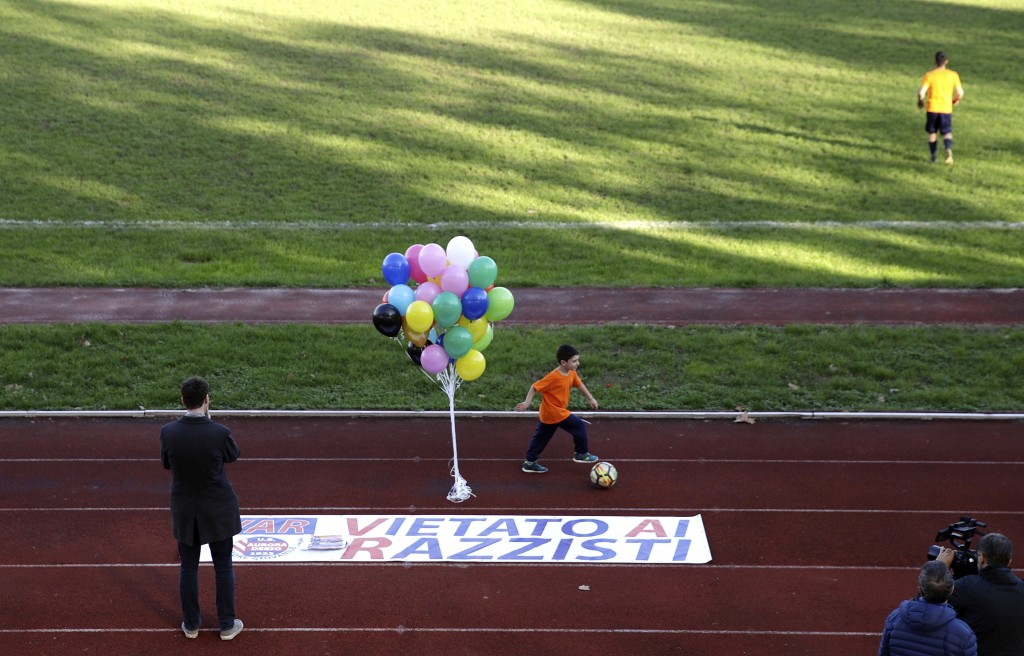 A boy runs past a banner reading in Italian ' Forbidden to racists ', prior to a youth team soccer match between Desio and Sovicese, at the municipal ...