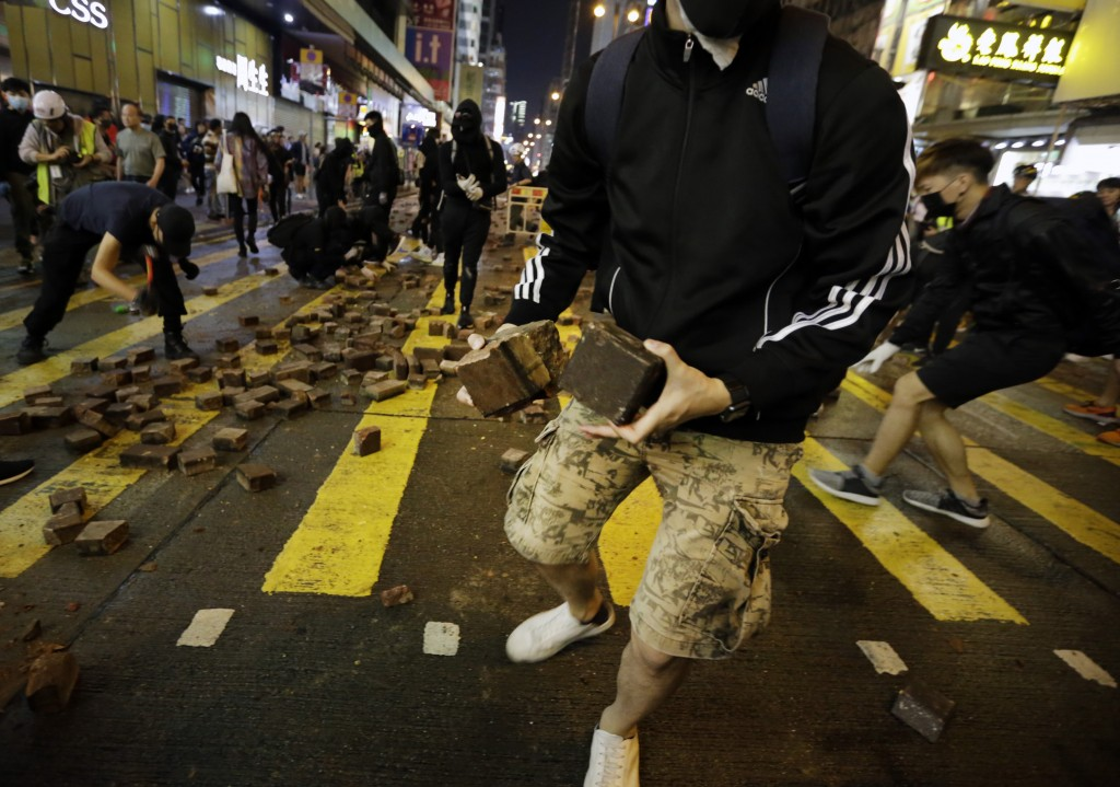 Protesters break up paving bricks to arm themselves during a clash with the police in Mong Kok, Hong Kong, Sunday, Nov. 10, 2019. Police fired tear ga...