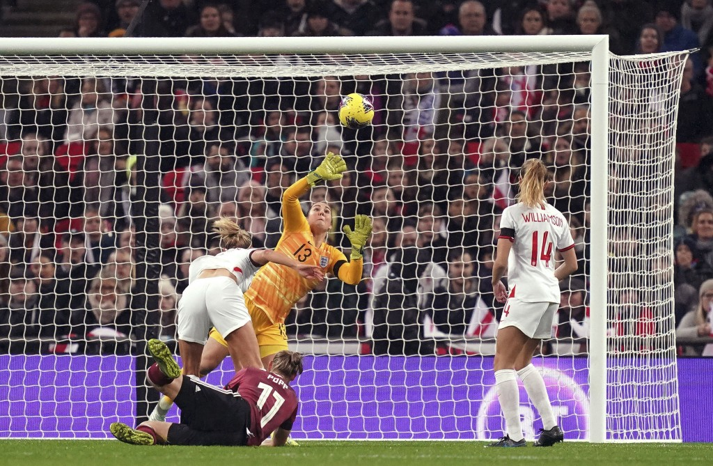 Germany's Alexandra Popp , left, scores her side's first goal during the Women's International Friendly soccer match between England and Germany, at W...