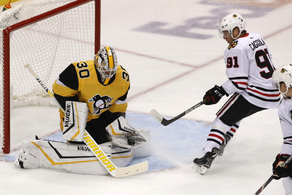 Pittsburgh Penguins goaltender Matt Murray (30) gloves a shot by Chicago Blackhawks' Drake Caggiula (91) during the first period of an NHL hockey game...