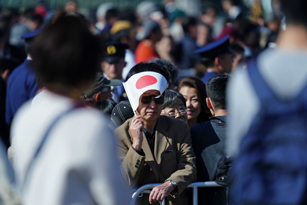 A visitor holds a Japanese national flag at the Imperial Palace before the royal parade of Japanese Emperor Naruhito and Empress Masako in Tokyo, Sund...
