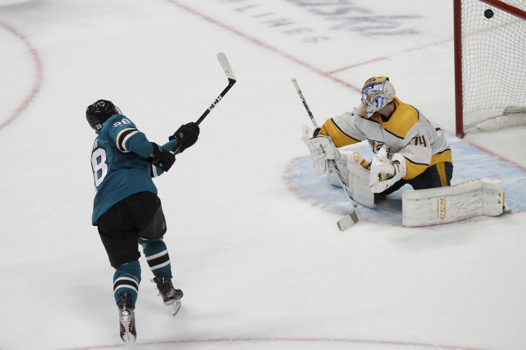 San Jose Sharks right wing Timo Meier, left, scores against Nashville Predators goaltender Juuse Saros (74) in the shootout of an NHL hockey game in S...