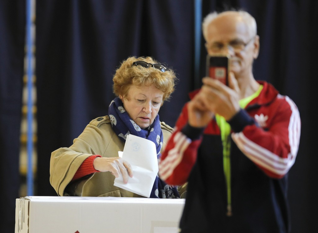 A man takes photos as a woman casts her vote in Bucharest, Romania, Sunday, Nov. 10, 2019. Voting got underway in Romania's presidential election afte...
