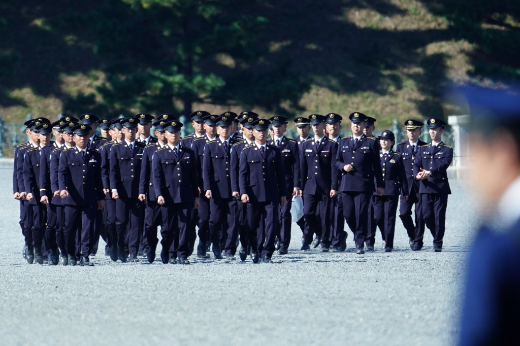 CORRECTS TO JAPAN SELF-DEFENSE FORCES' MEMBERS - Japan Self-Defense Forces' members walk in formation as they stand guard at the Imperial Palace befor...