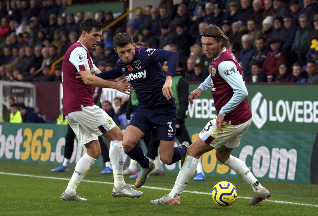West Ham United's Aaron Cresswell, centre and Burnley's Jeff Hendrick, right, battle for the ball during the English Premier League soccer match betwe...