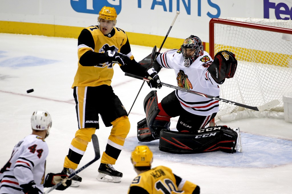 Pittsburgh Penguins' Evgeni Malkin (71) cannot get his stick on a shot in front of Chicago Blackhawks goaltender Corey Crawford (50) during the first ...
