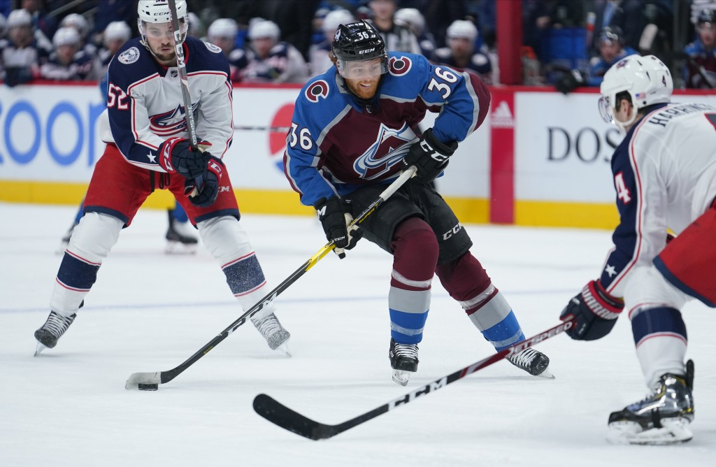Colorado Avalanche center T.J. Tynan (36) moves the puck between Columbus Blue Jackets center Emil Bemstrom (52) and Scott Harrington (4) during the s...