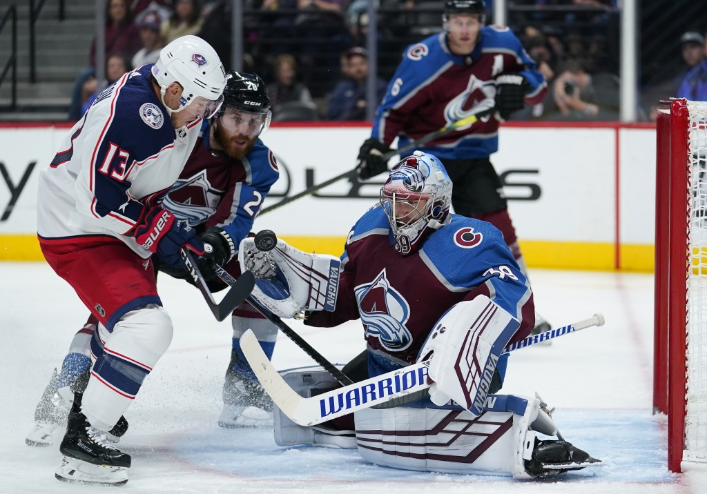 Colorado Avalanche goaltender Pavel Francouz (39) eyes the puck hit off the stick of Columbus Blue Jackets right wing Cam Atkinson (13) as Colorado Av...
